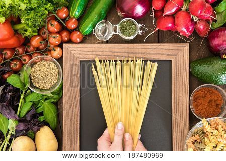 Overhead View Of Food Composition Ready To Cooking Pasta For Dinner. Human Hands Holding Pasta Over
