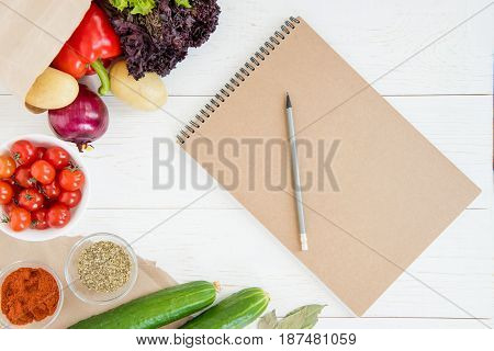 Top View Of Blank Notebook And Pencil With Fresh Raw Vegetables On Wooden Table