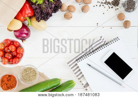 Top View Of Smartphone With Blank Screen, Empty Notebook With Pencil, Kitchen Towel And Fresh Ingred