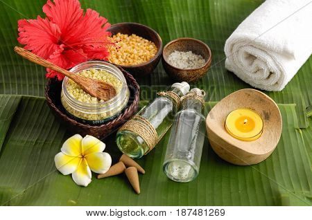 Tropical spa setting and banana leaf ,towel, spoon,red flower