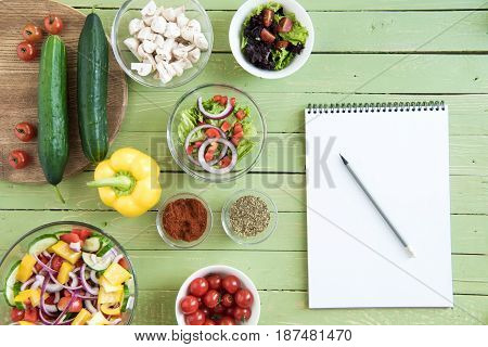 Top View Of Fresh Raw Vegetables And Salads In Bowls And Blank Notebook With Pencil On Wooden Table