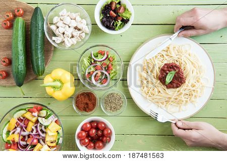 Close-up Partial View Of Person Holding Fork And Knife While Eating Spaghetti With Sauce And Basil A