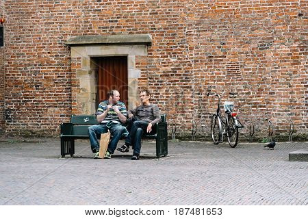 Utrecht Netherlands - August 4 2016: Two men sitting on a publick bench in historic centre of Utrecht the Netherlands