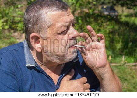 Portrait of Ukrainian senior peasant smoking cigarette rolled by himself