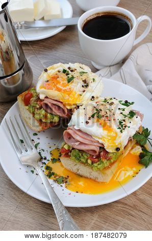 poached eggs with avocado tomatoes slices of ham on a baguette for breakfast
