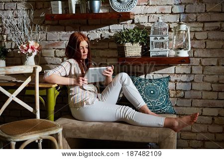 Young woman using tablet computer at home.