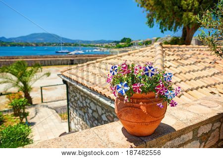 Clay jug with magenta flowers on stone wall. Classical yachts in Mediterranean sea. Kerkyra castle. Greece flag white blue colors flowers. Greece holidays vacations tours famous sightseeing