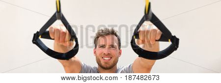 Fitness man banner suspension resistance straps training. Athlete holding handles doing inclined pull-ups for back and biceps muscles at gym. Panorama horizontal crop.