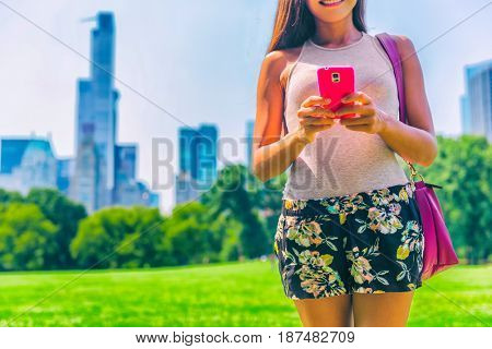 New York City lifestyle mobile phone woman texting sms on smartphone. in Central Park, NYC. USA summer travel.
