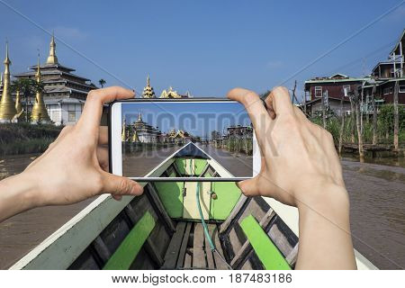 Tourist taking a photo with smartphone on a boat while visiting Indein Village in Myanmar