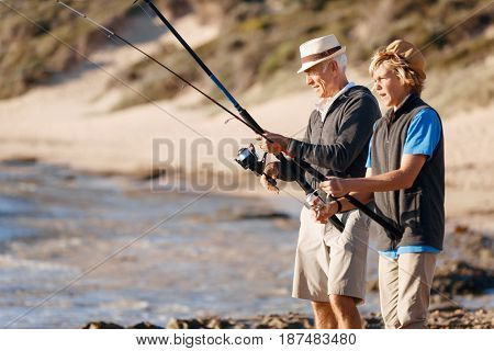 Senior man fishing with his grandson