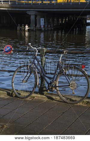 Bike is parked near the canal under the sign «no bikes»