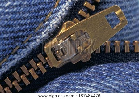 The zipper of a pair of jeans in close up.