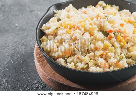 Cous Cous whit meat and vegetables in frying pan over gray stone background