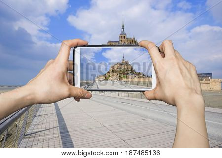 Tourist taking a photo of Mont Saint-Michel with smartphone in Normandy, France
