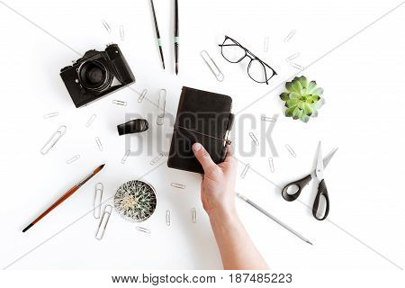 Partial Top View Of Human Hand Holding Wallet And Various Office Supplies And Plant Isolated On Whit