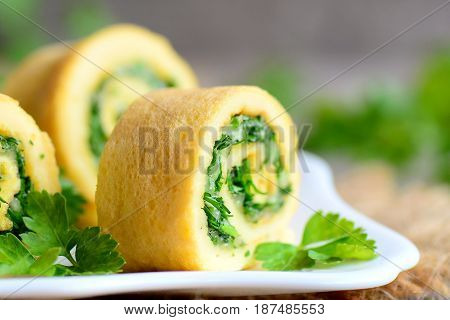 Homemade cheese and herbs stuffed omelette. Cut omelette with grated cheese and finely chopped herbs. Delicious and savoury breakfast omelette recipe. Rustic style. Closeup