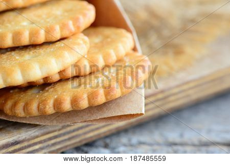 Dry salty cracker biscuits in a wrapping paper and wooden board. Crunchy savory cookies snack idea for children or adults. Rustic style. Closeup