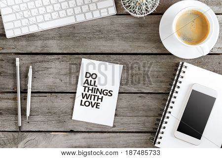 Flat Lay With Do All Things With Love Motivational Quote On Modern Workplace With Wireless Devices