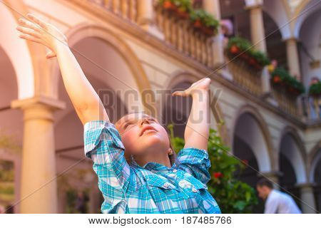 The Girl Raises Her Arms Admiringly Up To The Sunlight