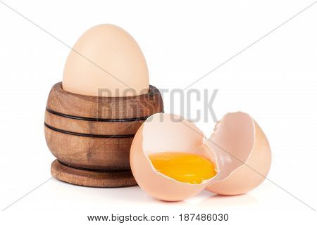 whole egg and broken egg in a wooden bowl isolated on white background.