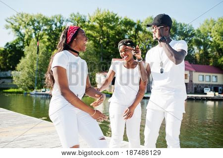 Three Stylish, Cheerful And Trendy African American Friends, Wear On White Clothes. Street Fashion O