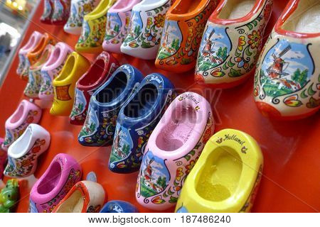 A collection of clogs in various colours with lovely decorations hanging on a wall.