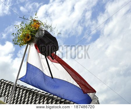 A schoolbag and a bouquet of sunflowers are hanging from a Dutch flag to show that the owner has finished school.