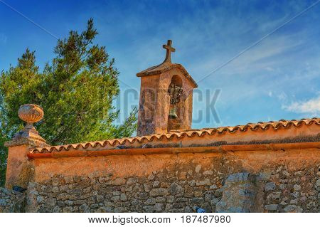 Church tower with bell in Spanish style against a blue sky.
