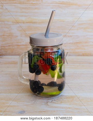 Detox infused water with lime lemons strawberries blueberries and mint in mason jar on wooden background. Delicious refreshing summer fruit berry drink. Healthy lifestyle detox diet loss weight concept.
