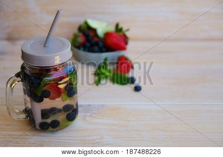 Detox infused water with lime lemons strawberries blueberries and mint in mason jar on wooden background. Delicious refreshing summer fruit berry drink. Healthy lifestyle detox diet loss weight concept.Copy space.