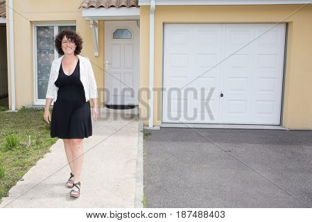 Middle-aged Woman In Front Of Her House