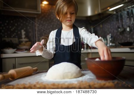 Cute little girl flour a dough in the kitchen. Horizontal indoors shot.