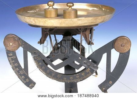 An oldfashioned scale with two small weights on it.
