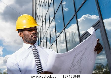 Low Angle View Of Professional Architect In Hard Hat Holding Blueprint Outside Modern Building