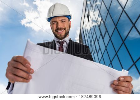 Low Angle View Of Smiling Bearded Architect Holding Blueprint And Looking At Camera