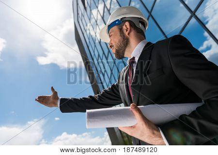Low Angle View Of Professional Architect In Hard Hat Holding Blueprint And Gesturing