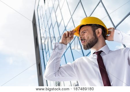 Side View Of Confident Professional Architect In Hard Hat Against Building