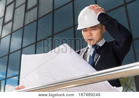 Portrait Of Confused Professional Architect In Hard Hat Looking At Blueprint