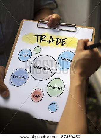 Hands working on notepad regarding business trading
