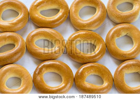 A lot of baked bagels in a raw on white background, close-up
