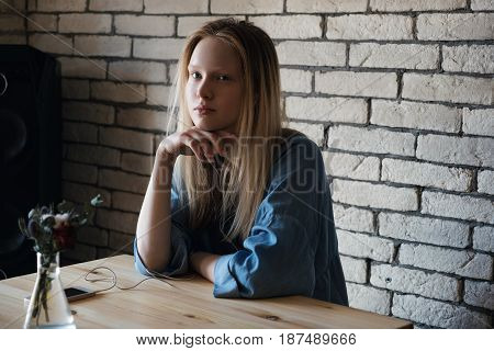 Blond girl in a blue shirt is sitting with headphones and looking thoughtfully away, with her hand on her chin