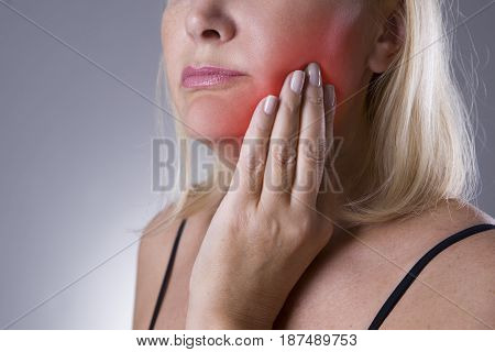 Aged woman with toothache teeth pain closeup on gray background
