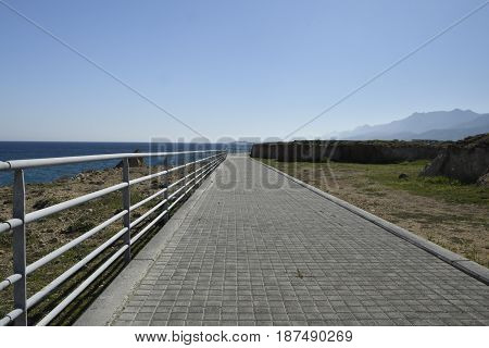 Boardwalk at the seashore outside the village Lapta in the North of Cyprus with clear blue water and blue sky.