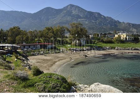Bay with a beach near Lapta village with clear blue water and blue sky and Kyrenia mountains in the North of Cyprus in background.