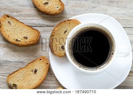 Crunchy toasted bread with raisins and cup of coffee top view, wooden background