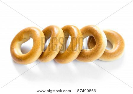 Five dry bagels isolated on white background, closeup