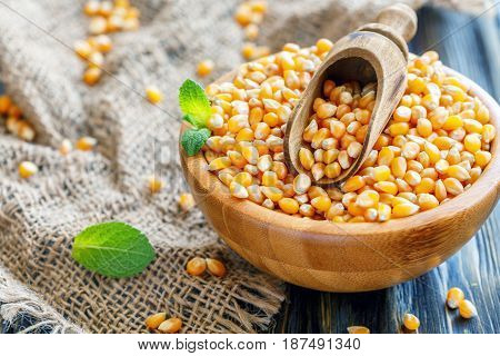 Wooden Bowl With Corn For Popcorn And A Scoop.