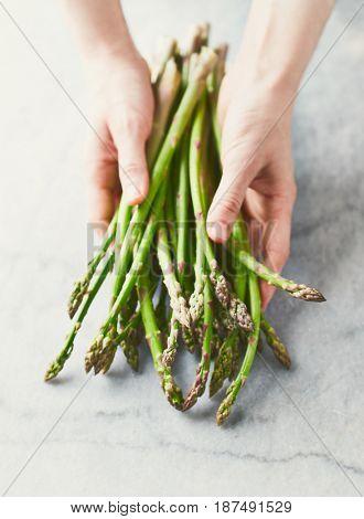 Hands holding fresh Green Asparagus
