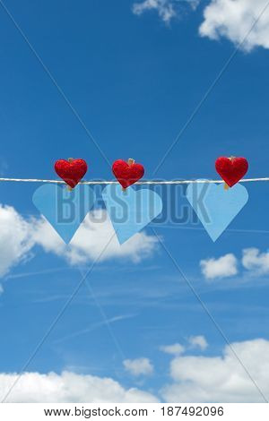 Three hearts with clothes pegs and three hearts of paper on a cord